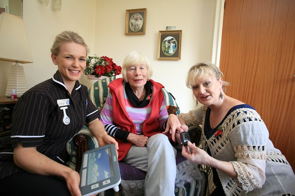 Community Matron Kate Philpotts, Pauline Priddy, and Suzie Lindesay with the unit which sends details of Pauline's health to Community Nursing professionals.