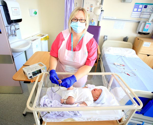 Ally Lewis, transitional care support worker at WVT, and new born baby Erin Callachan, with the pulse oximetry machine in use on the maternity ward at Hereford County Hospital.