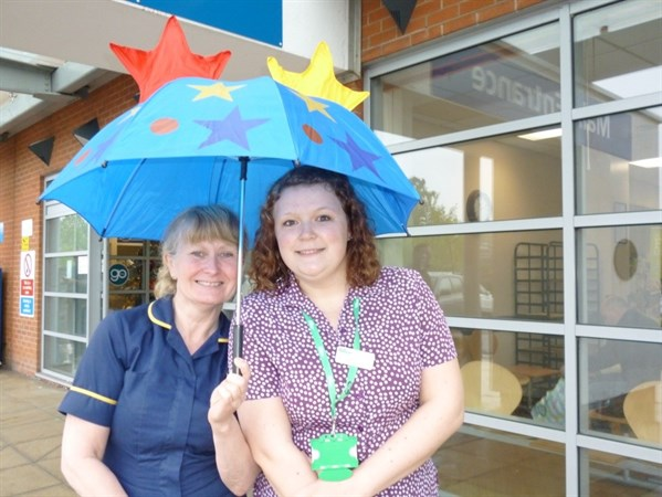 Left To Right Pauline Featonby - Lead Dermatology Clinical Nurse Specialist , And Sophie Davis – Macmillan Skin Cancer Support Worker Standing Under A Sun Umbrella.